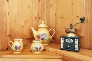 EIn historisches Kaffeegeschirr neben ein manuellen Kaffeemühle.